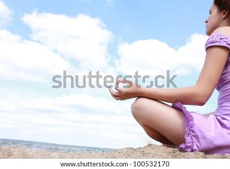 Beautiful girl practicing yoga on the beach