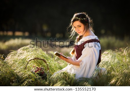 Beautiful girl reading a book in a country setting, dressed in historical clothing
