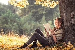 beautiful girl reading a book in autumn forest , autumn season concept and reading