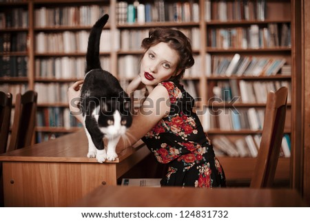 Beautiful girl reading a book in the library, next to the cat