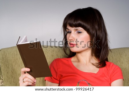 beautiful girl reading a book while sitting on the couch
