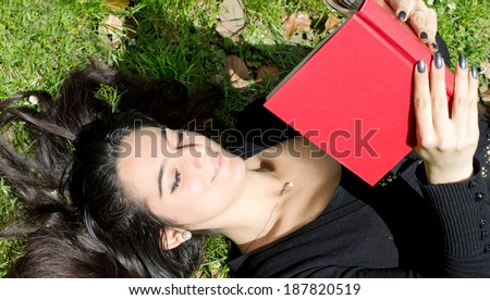 beautiful girl reading a funny book in outdoor scene