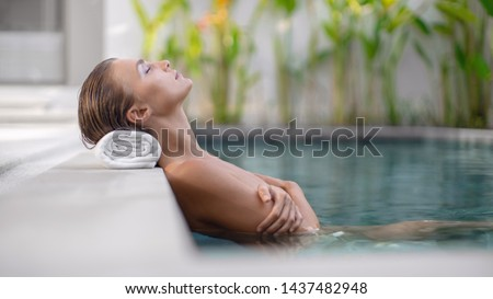 Beautiful girl relaxes around the pool. Spa