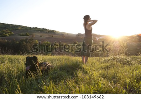 Beautiful girl relaxes in the sunlight whilst walking her dog