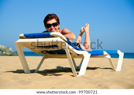 beautiful girl relaxes on a lounger in sunglasses
