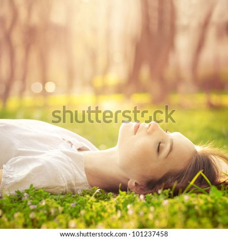 beautiful girl relaxing lying on the grass in the garden
