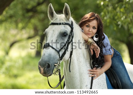 Beautiful girl rides a horse in the summer park