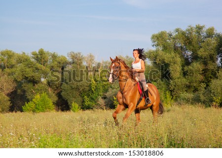 Beautiful girl riding a horse in countryside