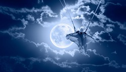 Beautiful girl riding a swing on the space on a full moon at night