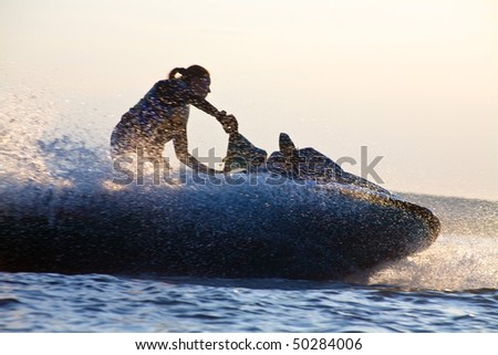 beautiful girl riding her jet skis in the sea at sunset. silhouette