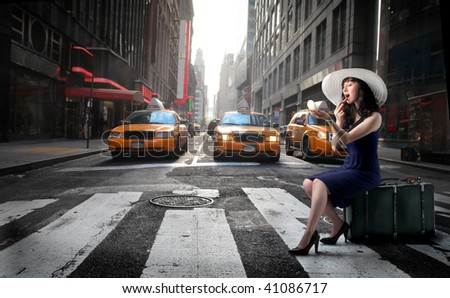 beautiful girl seated on suitcase and waiting for a taxi in a city street