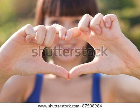 Beautiful girl show love sign outdoor