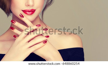 Beautiful girl showing red  manicure nails . makeup and cosmetics