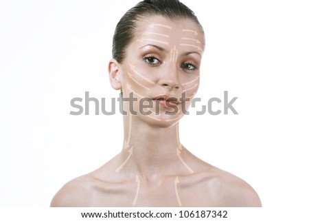 Beautiful girl shows a schematic drawing of cream on the face and neck. Portrait of beautiful woman with brown eyes.