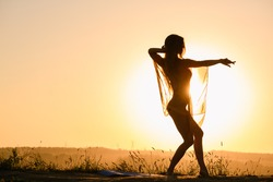 Beautiful girl silhouette dancing exercise against warm sun in transparent cloth, female fit body curves