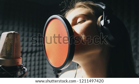 Beautiful girl singing in sound studio. Young singer emotionally recording new song. Lady sings to microphone. Working of creative musician. Show business concept. Slow motion Close up. #1211497420