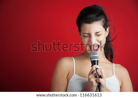 Beautiful girl singing with microphone against red background with copy space.