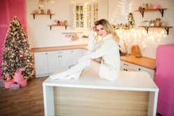 beautiful girl sits on a table in the studio in a white tunic, New Year's photo session