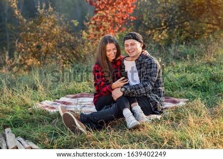 Beautiful girl sits on her boyfriend lap and using smart phone on the lawn in the park. Hipster modern couple have a chatting with their friends sitting in the nature.