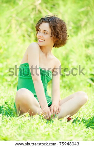 Beautiful girl sits on lawn.