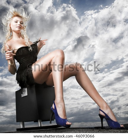Beautiful girl sitting against cloudy sky