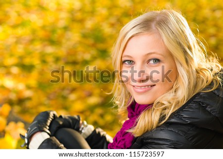 Beautiful girl sitting, autumn color leaves on the background, horizon format