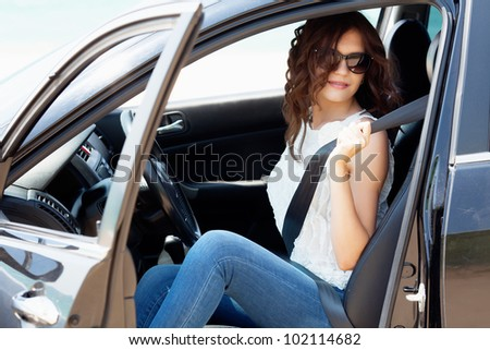 Beautiful girl sitting in the black car
