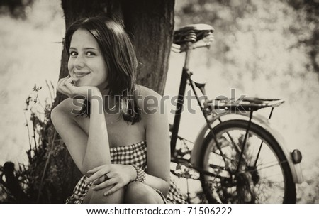 Beautiful girl sitting near bike and tree at rest in forest. Photo in old colour image style.