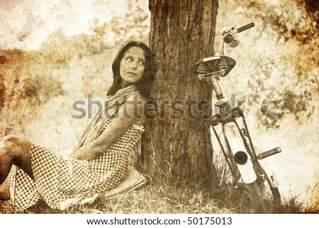 Beautiful girl sitting near bike and tree at rest in forest. Photo in old image style.