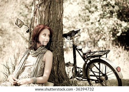 Beautiful girl sitting near bike and tree at rest in forest. Photo in retro style.