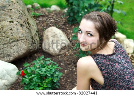 Beautiful girl sitting near the bush of red roses and big stone in garden