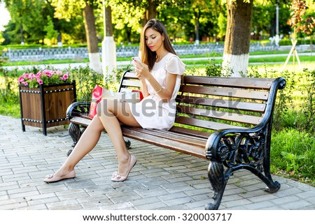 Beautiful girl sitting on a bench, brunette in a pink dress, fashion life style with your phone writes a message on social networks, sunny day in the park, relaxing, after work business woman.