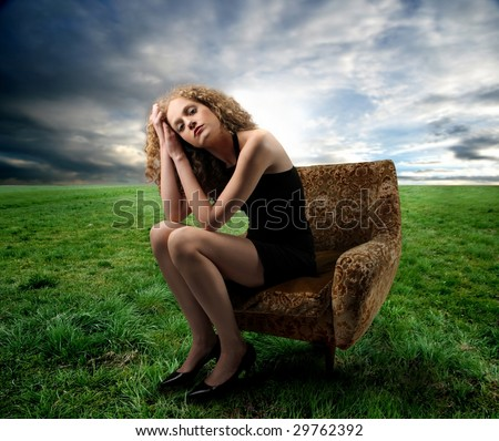 beautiful girl sitting on an armchair in a grass field