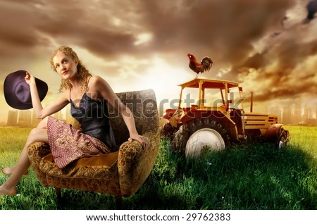 beautiful girl sitting on armchair in a grass field with a tractor - stock photo