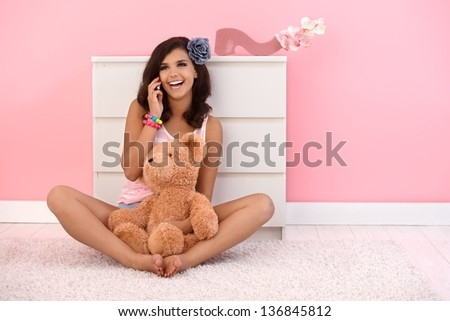 Beautiful girl sitting on floor with teddy bear, talking on mobile phone.