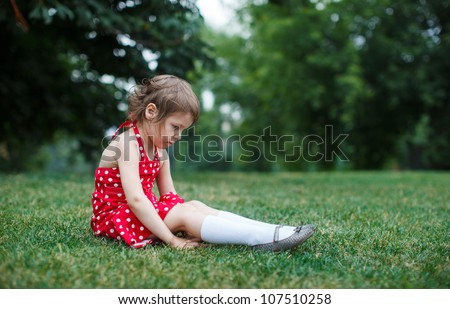 Beautiful girl sitting on grass in the park - stock photo