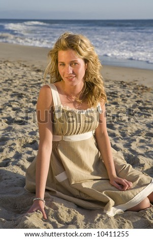 Beautiful Girl Sitting on the Beach at Sunset