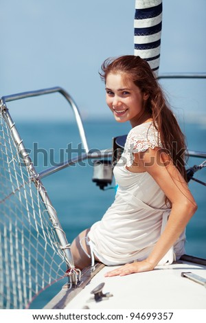 Beautiful girl sitting on the bow of a sailing yacht.