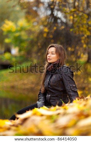 Beautiful girl sitting on the leaves near the pond