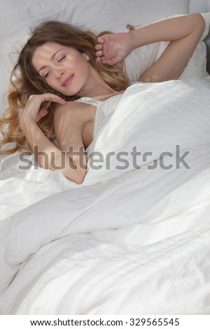 Beautiful girl sleeping in the early morning in my warm cozy bed, she wakes up and smiles.   Woman lying on the back in white bed 6, the sun shines on the bed through the blinds.