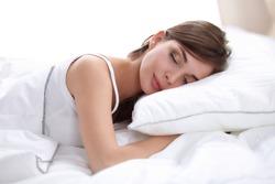 Beautiful girl sleeps in the bedroom, lying on bed, isolated