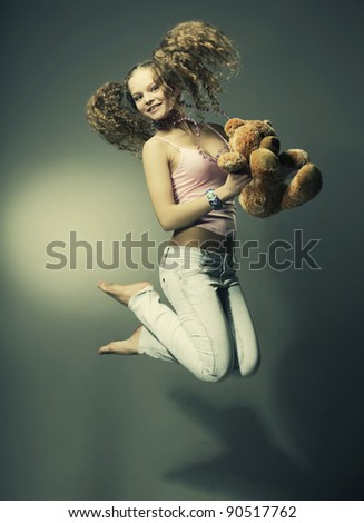 Beautiful girl smiling holding a gift - toys, jump