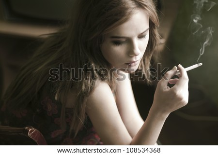 beautiful girl smokes and sad