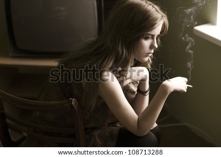 beautiful girl smokes at home