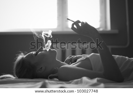 beautiful girl smokes in bed