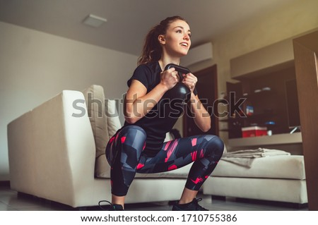 Beautiful  girl sport at home . Fitness exercise with kettlebell, smart training, exercise, home workout