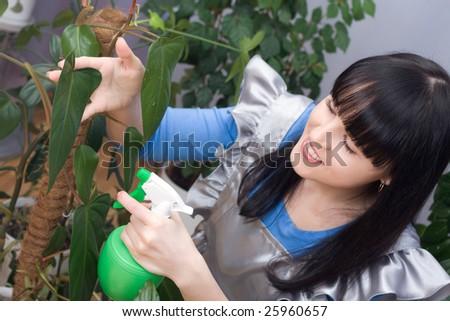 Beautiful girl sprays water room green plants