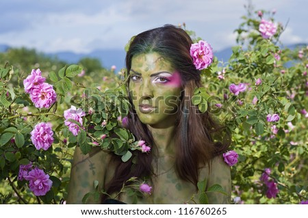 Beautiful girl standing in rose field