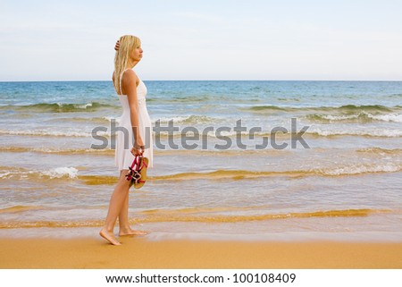 Beautiful girl standing in the evening by the sea