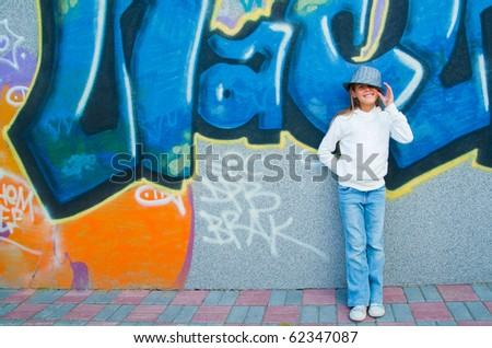 Beautiful girl standing near a wall with graffiti. Outside